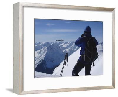 A Back-Country Skier Watches a Heli-Ski Chopper Approach a Peak-Skip Brown-Framed Photographic Print