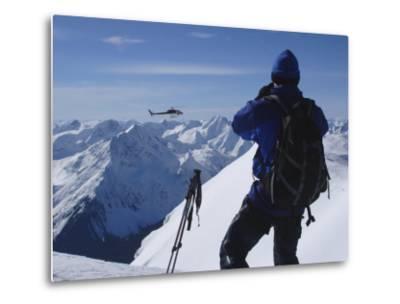A Back-Country Skier Watches a Heli-Ski Chopper Approach a Peak-Skip Brown-Metal Print