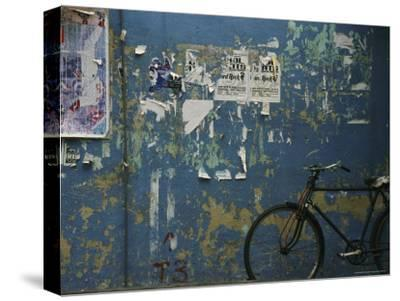 A Bicycle is Parked against a Blue Wall-Todd Gipstein-Stretched Canvas Print