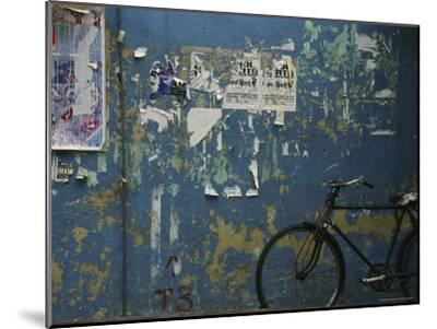 A Bicycle is Parked against a Blue Wall-Todd Gipstein-Mounted Photographic Print