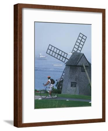 A Man on a Bicycle Passing a Windmill on the Shore in Cape Cod-Darlyne A^ Murawski-Framed Photographic Print