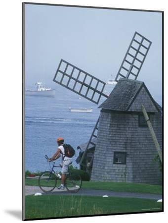 A Man on a Bicycle Passing a Windmill on the Shore in Cape Cod-Darlyne A^ Murawski-Mounted Photographic Print