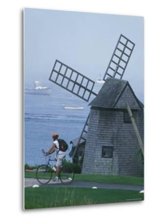 A Man on a Bicycle Passing a Windmill on the Shore in Cape Cod-Darlyne A^ Murawski-Metal Print