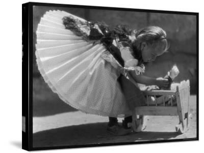 Young Romanian Girl Leans to Pick up Her Small Doll from a Beautifully Crafted Wooden Crib--Stretched Canvas Print