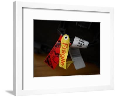 A Fragile Tag is Shown Hanging on a Piece of Baggage-Stephen Alvarez-Framed Photographic Print