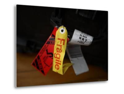 A Fragile Tag is Shown Hanging on a Piece of Baggage-Stephen Alvarez-Metal Print
