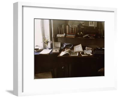 National Geographics Rest on a Desk Near a Typewriter-Maynard Owen Williams-Framed Photographic Print