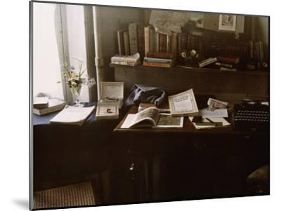 National Geographics Rest on a Desk Near a Typewriter-Maynard Owen Williams-Mounted Photographic Print