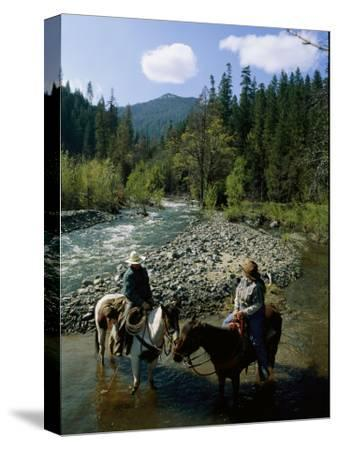 Horseback Riders Stand in Coffee Creek-Phil Schermeister-Stretched Canvas Print