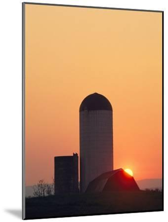 Twilight View of a Barn and Silo Silhouetted against the Sun-Kenneth Garrett-Mounted Photographic Print