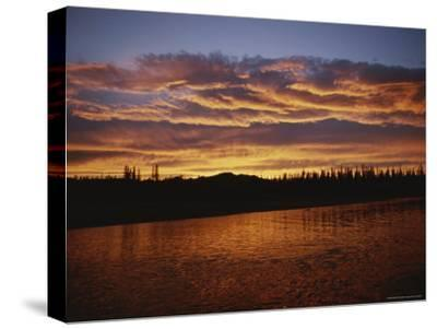 An Intense Sunset Colors Clouds and the Water of the Mackenzie River-Raymond Gehman-Stretched Canvas Print
