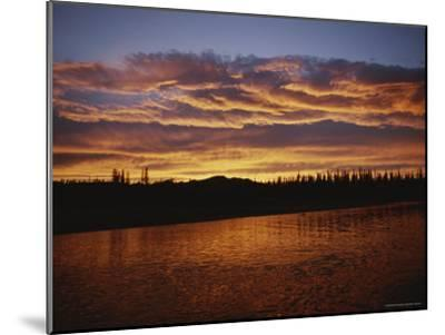 An Intense Sunset Colors Clouds and the Water of the Mackenzie River-Raymond Gehman-Mounted Photographic Print