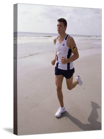 Young Man Jogging on the Beach--Stretched Canvas Print
