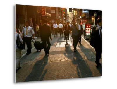 Japanese Commuters Walk Through a Tokyo Street on Their Way to the Train Stations-David Guttenfelder-Metal Print