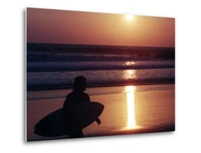 A Surfer is Silhouetted by the Setting Sun as He Leaves the Pacific Ocean on Venice Beach--Metal Print