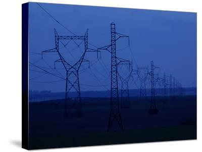 Tall Towers Supporting Power Lines in a Dark Blue Sky--Stretched Canvas Print