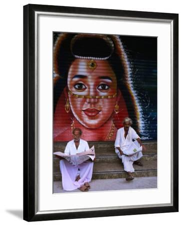 Local Men Read Newspapers in Front of Painted Shutter, Kozhikode, Kerala, India-Greg Elms-Framed Photographic Print