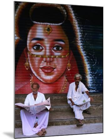 Local Men Read Newspapers in Front of Painted Shutter, Kozhikode, Kerala, India-Greg Elms-Mounted Photographic Print