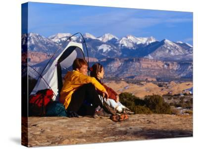 Couple Camping at Slickrock with Snow-Capped Peaks in the Background, Utah, USA-Cheyenne Rouse-Stretched Canvas Print
