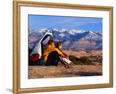 Couple Camping at Slickrock with Snow-Capped Peaks in the Background, Utah, USA-Cheyenne Rouse-Framed Photographic Print