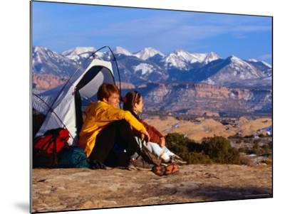 Couple Camping at Slickrock with Snow-Capped Peaks in the Background, Utah, USA-Cheyenne Rouse-Mounted Photographic Print