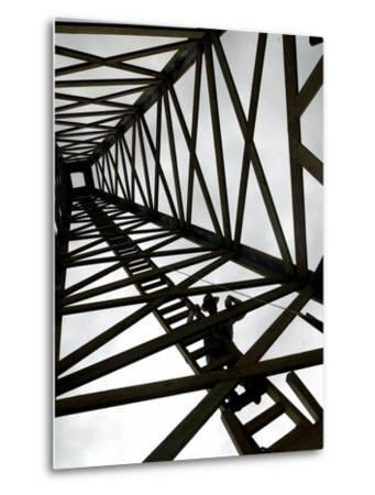 A Reenactor is Silhouetted Inside a Replica of the Spindletop Oil Derrick--Metal Print
