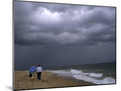 Daughter and Mother Walk Along a Beach, Storm Clouds Darken the Sky-Brian Gordon Green-Mounted Photographic Print