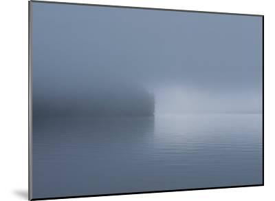 Thick Fog Hangs Over Eerily Calm Water Where a Point of Land Juts Out-Bill Curtsinger-Mounted Photographic Print