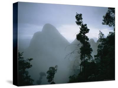 Peak of Gunung Budda Through Early Morning Fog-Stephen Alvarez-Stretched Canvas Print