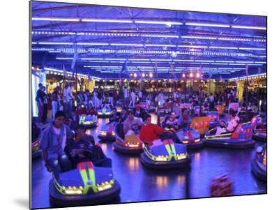 Teenagers Ride Bumper Cars under Neon Blue Lights-Dominic Bonuccelli-Mounted Photographic Print