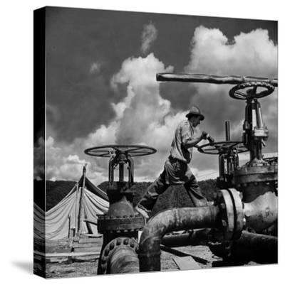 Worker Opening up a Pipeline to Let the Oil Flow-Thomas D^ Mcavoy-Stretched Canvas Print