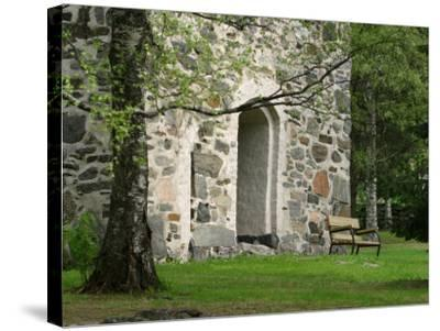 Wooden Bench in Peaceful Garden in Front of Stone Building--Stretched Canvas Print