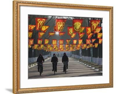 Bicycle Riders at Entranceway to Festival, Ice and Snow Festival, Harbin, Heilongjiang, China-Walter Bibikow-Framed Photographic Print