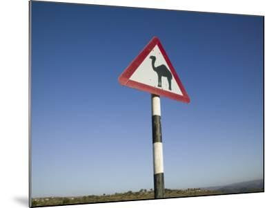 Oman, Dhofar Region, Salalah, Camel Crossing Sign in the Dhofar Mountains-Walter Bibikow-Mounted Photographic Print
