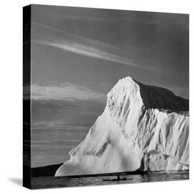 Native Man in Kayak Sitting in Water Next to Iceberg--Stretched Canvas Print