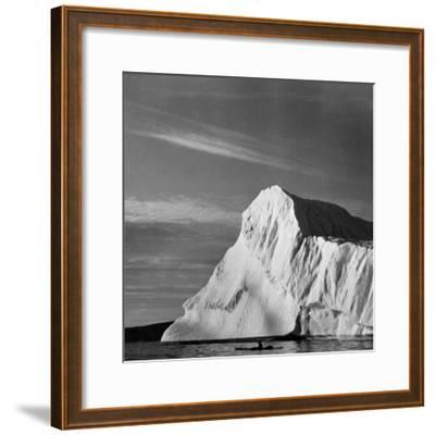 Native Man in Kayak Sitting in Water Next to Iceberg--Framed Photographic Print