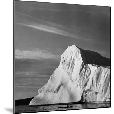 Native Man in Kayak Sitting in Water Next to Iceberg--Mounted Photographic Print