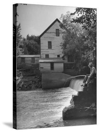Man Fishing Beside a Waterfall and a 100 Year Old Mill-Bob Landry-Stretched Canvas Print