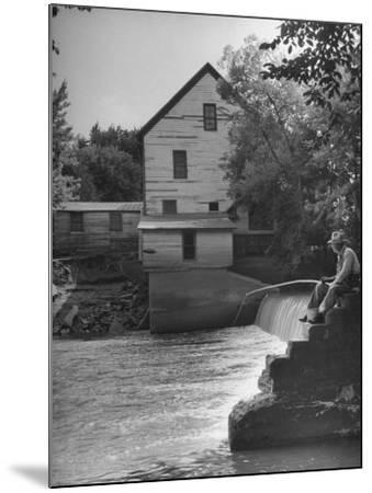 Man Fishing Beside a Waterfall and a 100 Year Old Mill-Bob Landry-Mounted Photographic Print