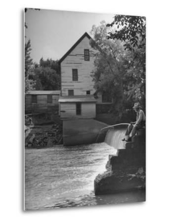 Man Fishing Beside a Waterfall and a 100 Year Old Mill-Bob Landry-Metal Print