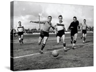 Soccer Players Running after the Ball During a Game-A^ Villani-Stretched Canvas Print