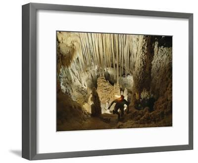 A spelunker explores a cave wearing a lanterned helmet-Michael Nichols-Framed Photographic Print