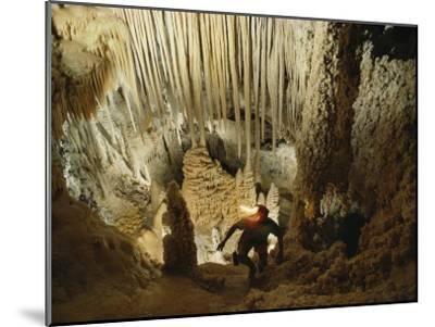 A spelunker explores a cave wearing a lanterned helmet-Michael Nichols-Mounted Photographic Print