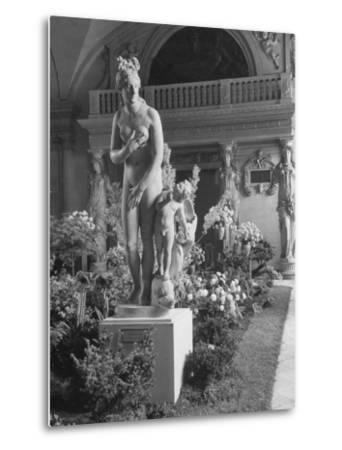 The Statue of Aphrodite and Eros in Louvre Museum During a Flower Show-Dmitri Kessel-Metal Print