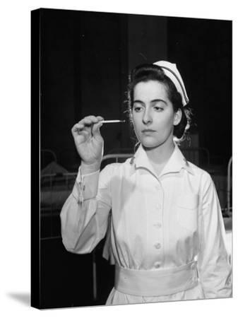 US Navy Nurse in Uniform Reading a Thermometer--Stretched Canvas Print