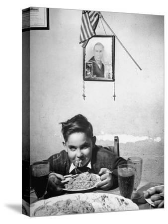 Boy Eating Spaghetti under Picture of His Brother Who Died During Invasion of Sicily--Stretched Canvas Print
