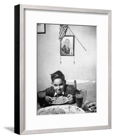 Boy Eating Spaghetti under Picture of His Brother Who Died During Invasion of Sicily--Framed Photographic Print