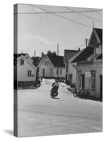 Motorcycle Going Down Street in Small Town--Stretched Canvas Print