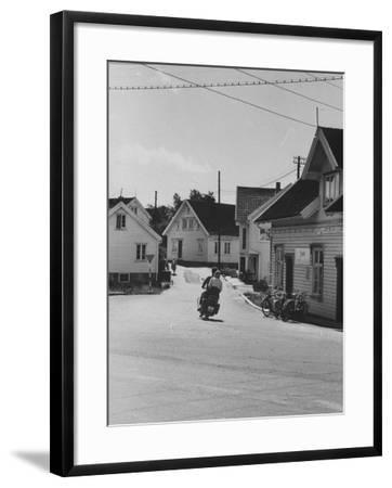 Motorcycle Going Down Street in Small Town--Framed Photographic Print