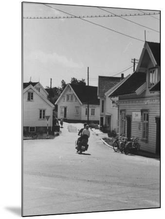 Motorcycle Going Down Street in Small Town--Mounted Photographic Print